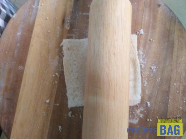 Quickly roll the bread slice with the help of a rolling pin, this just takes just 1 forward-backwards stroke.