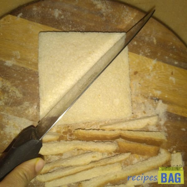 Remove the brown sides of the bread slices with the help of a knife and cut it into triangular pieces by making a slanted slit. (You can also cut the bread into squares by making horizontal and a vertical slit)
