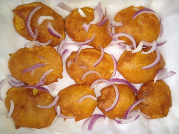 Sprinkle some chat masala and garnish with onions. That's it potato fritters are ready to be served.
